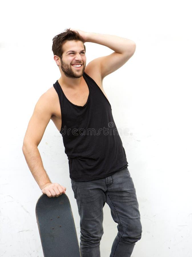 В стиле фанк парень держа скейтборд против белой предпосылки стоковые изображения
