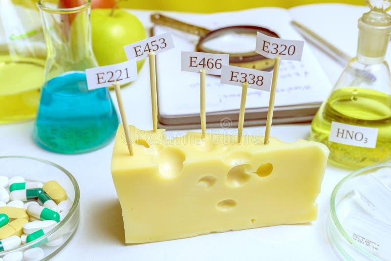 В сыре знаки с E-дополнениями кода Рядом на таблице склянка азотноводородной кислоты - главный нитрат Вредный стоковые изображения