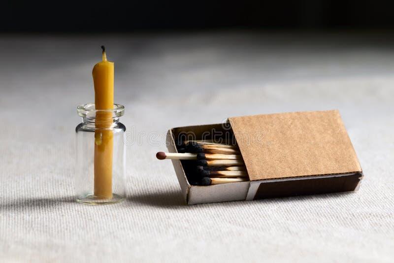 В темной комнате на таблице потухшая свеча Одна одиночная работая спичка среди, который сгорели вставлять из коробки символизируе стоковое фото