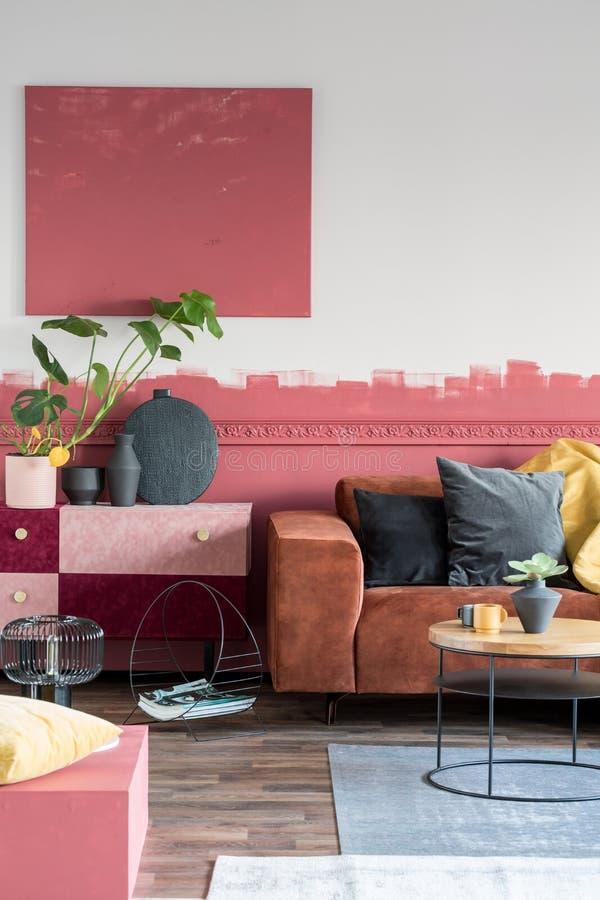 В уютной гостиной-салоне в роскошной салоне разместилась бутербродная и пастельно-розовая суматоха с черной вазой с зеленым листо стоковое изображение