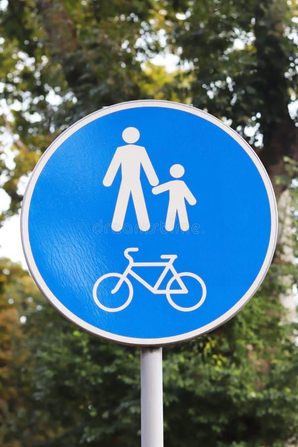 В форме кругл дорожный знак зона пешехода и велосипеда против предпосылки зеленой листвы Белые человеки подписывают и велосипед стоковая фотография
