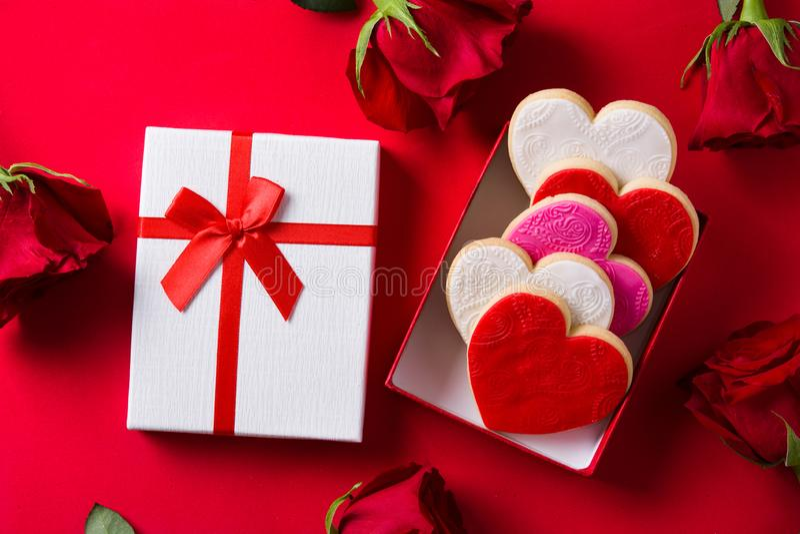 в форме Сердц печенья на день Валентайн и розы в подарочной коробке на красной предпосылке стоковая фотография rf