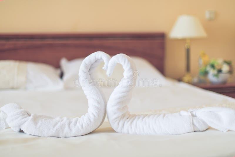 в форме Сердц полотенца лежат на кровати в гостинице стоковые фото