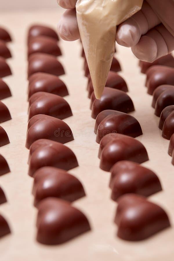 в форме Сердц шоколады будучи украшанным с gloved рукой стоковые изображения