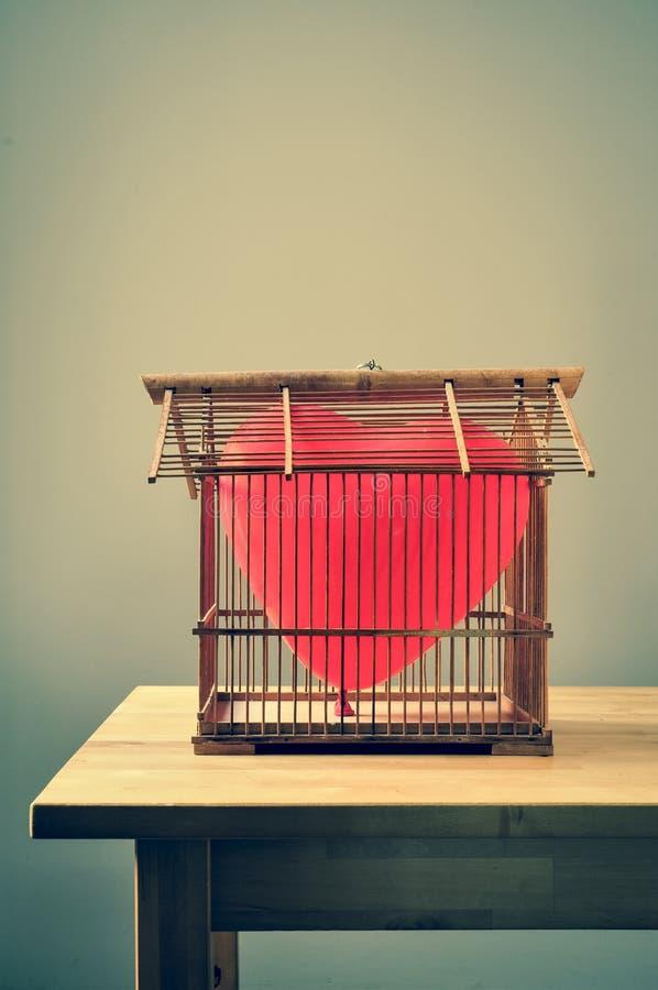 в форме Сердц воздушный шар в старом birdcage стоковые изображения