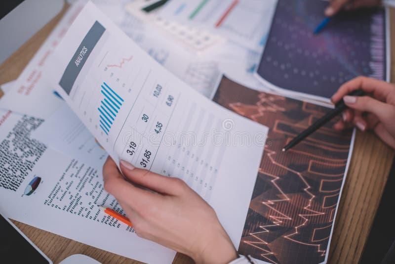 В центре внимания аналитиков, работающих за столом, находятся документы с графиками стоковая фотография rf