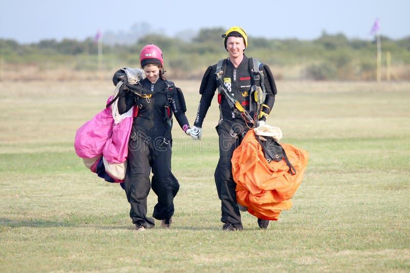 Влюбленность в воздухе! Skydivers человека и женщины идя рука об руку стоковые фото