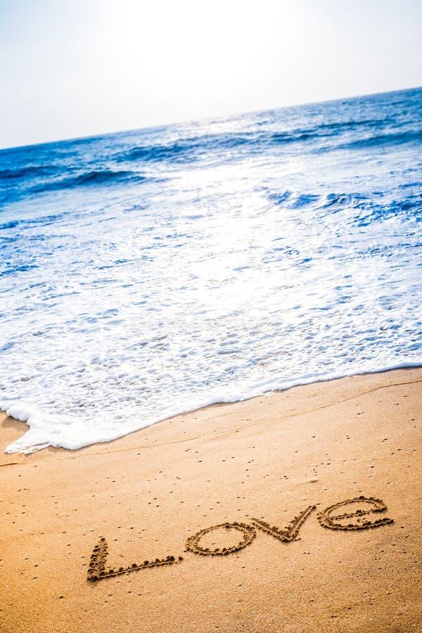 Влюбленность слова написанная в песке стоковая фотография rf