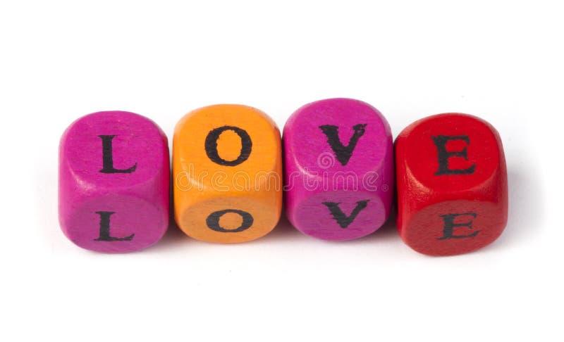 Влюбленность слова на пестротканых деревянных кубиках стоковое изображение rf