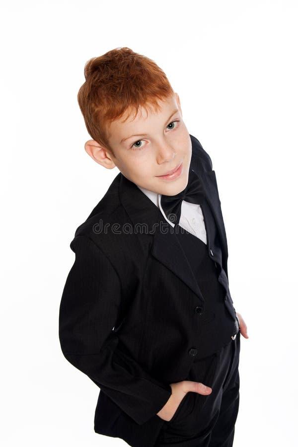 ?oy con el pelo rojo en un traje negro con la pajarita foto de archivo