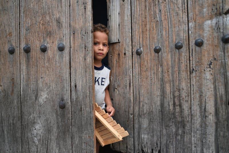Гавана, Куба, 14-ое августа 2018: Мальчик оставаясь на домашних воротах в Гаване стоковые изображения rf