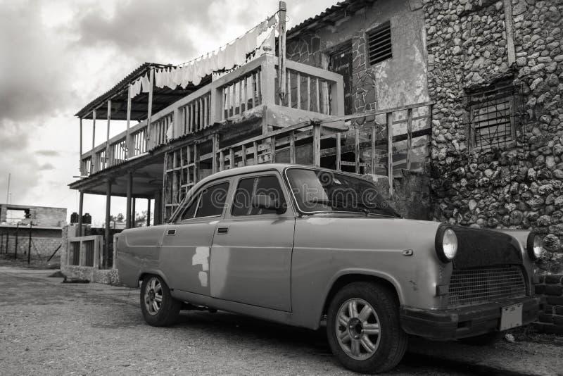 20/03/2015, Гавана, Куба: Старый complety изготовленный на заказ собранный автомобиль ржавеет прочь перед старым кубинским здание стоковая фотография
