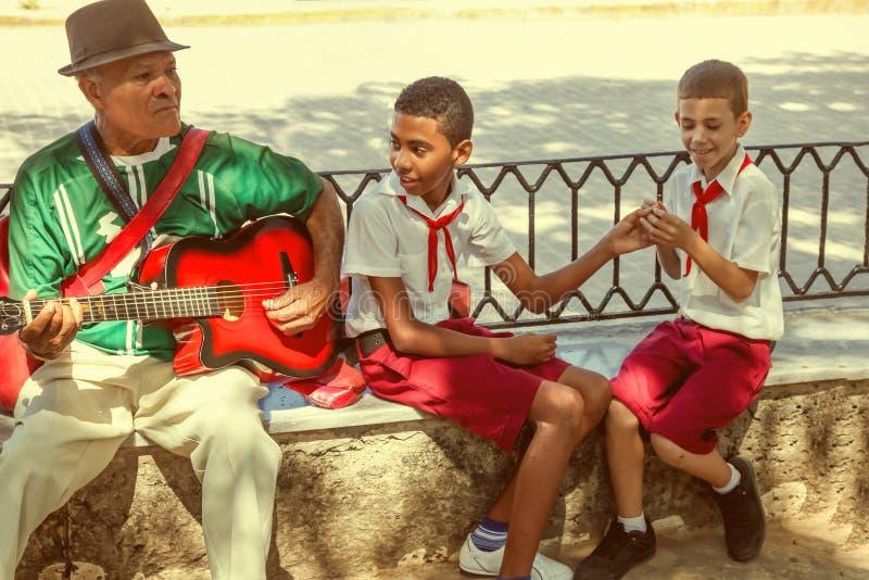 Гавана/Куба - SEPT. 2018: Старый музыкант играет гитару сидя близко до 2 кубинских зрачка - мальчики в красной и белой форме стоковая фотография