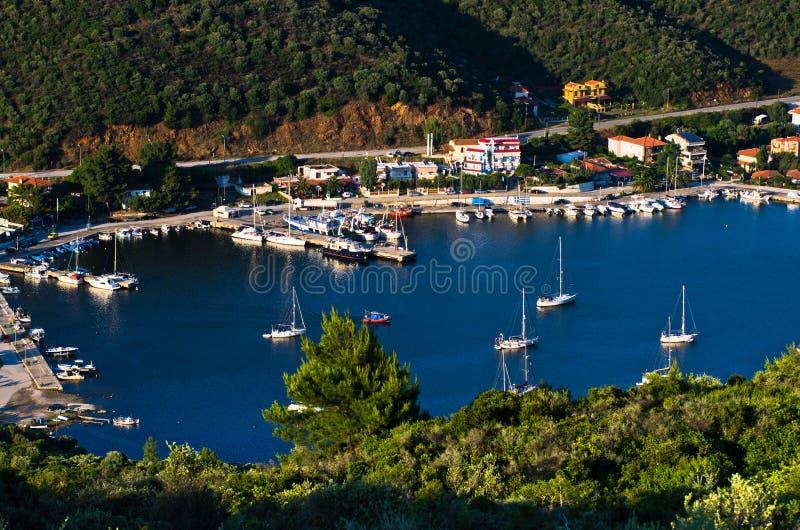 Гавань Порту Koufo с много поставленными на якорь парусниками на заходе солнца, западным побережьем Sithonia стоковая фотография