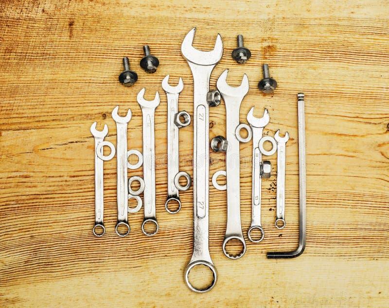 Гаечные ключи на деревянной доске, взгляд сверху стоковое фото