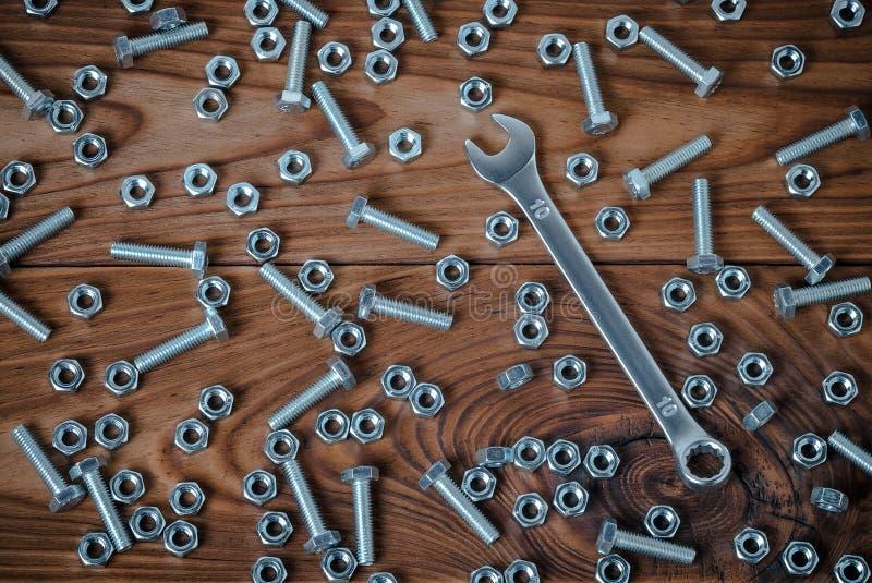 Гаечный ключ и гайки с болтами на деревянной поверхности стоковое фото