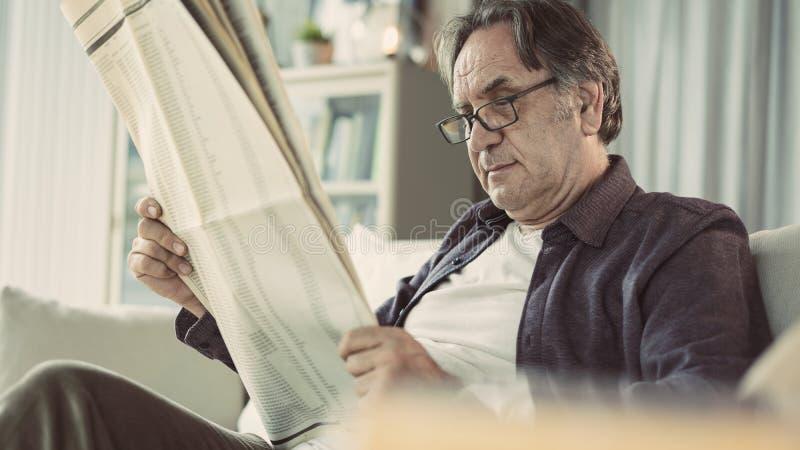 Газета чтения старшего человека дома стоковые фотографии rf