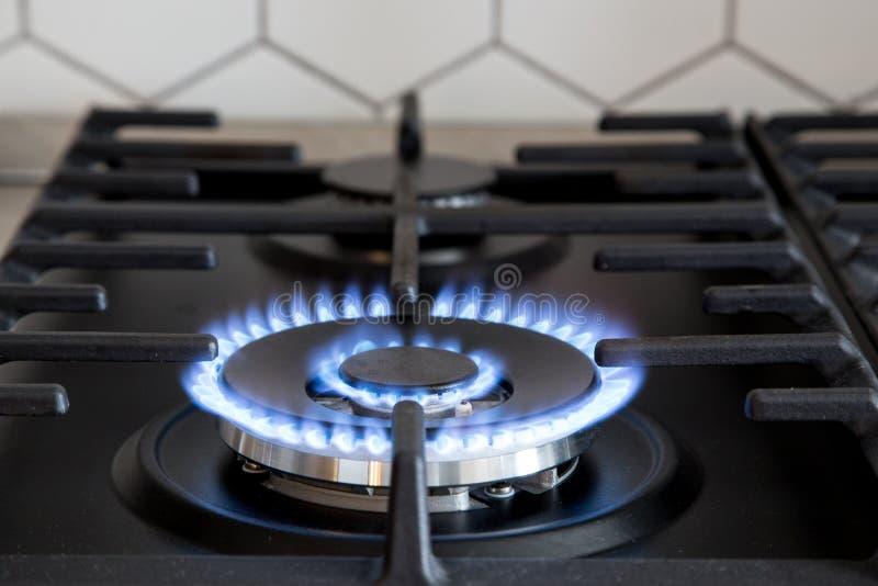 Газовая горелка на черной современной плите кухни плита газа кухни с горящим газом пропана огня стоковые фотографии rf