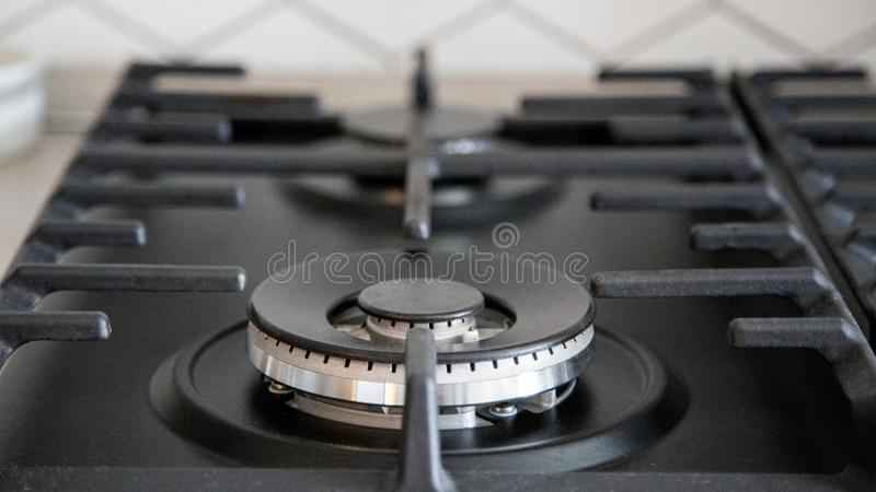 Газовая горелка на черной современной плите кухни плита газа кухни с горящим газом пропана огня стоковое изображение