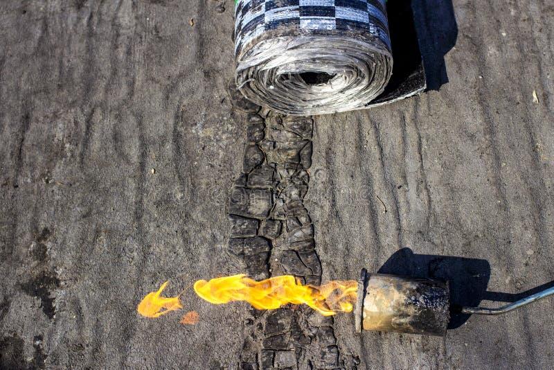 Газовая горелка с огнем и креном материала толя на запачканной предпосылке с влиянием bokeh стоковая фотография rf