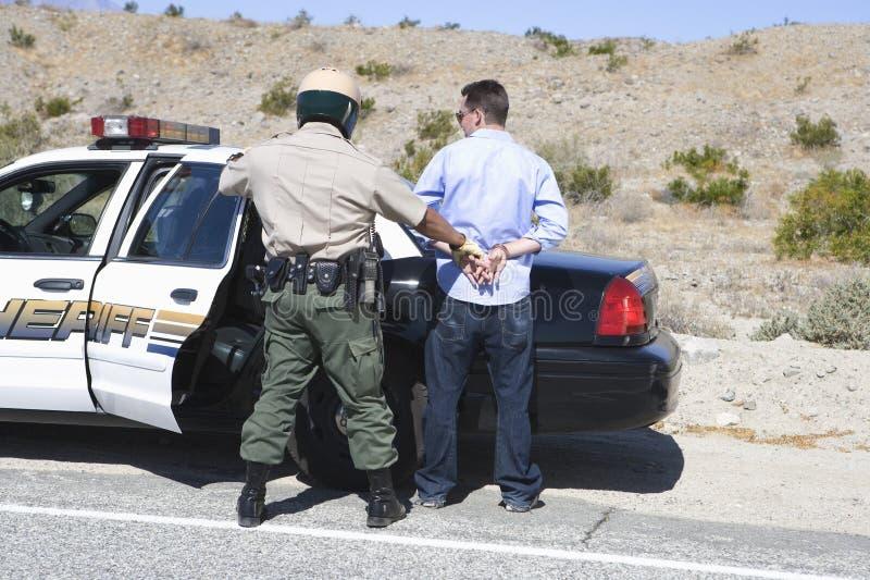 Гаишник арестовывая запойного водителя стоковые изображения