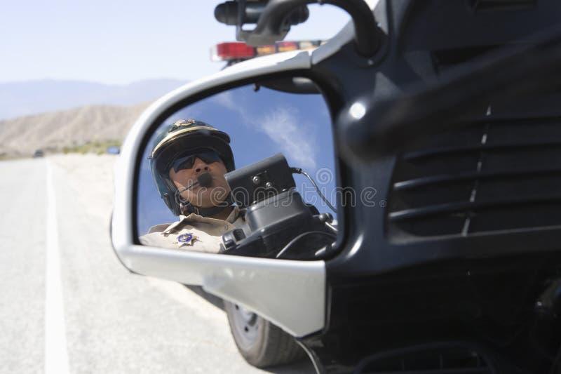 Гаишник отражая в зеркале взгляда со стороны стоковые изображения