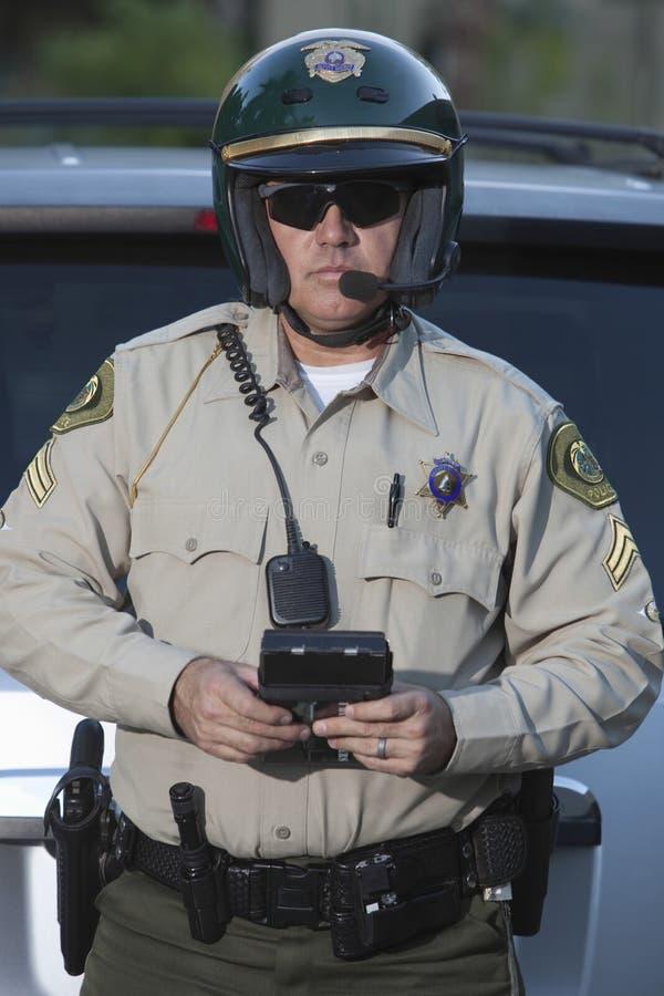 Гаишник при доска сзажимом для бумаги стоя против автомобиля стоковое фото rf