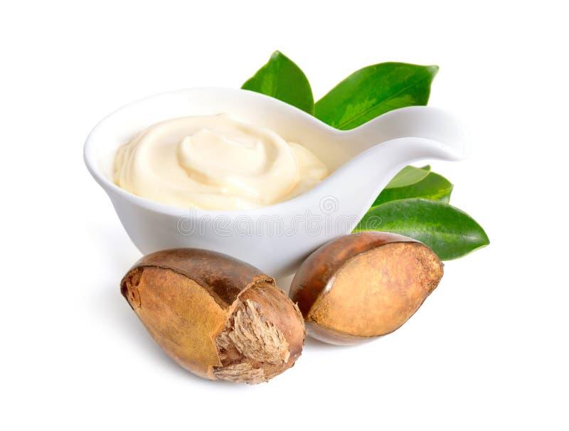 Гайки дерева ши с маслом или сливк в шаре Изолированный на белом ба стоковое фото rf