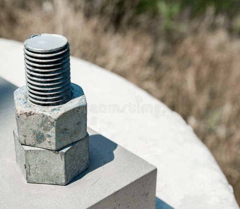2 гайки продетой нитку на болте прикрепленном для того чтобы цементировать блок стоковое изображение