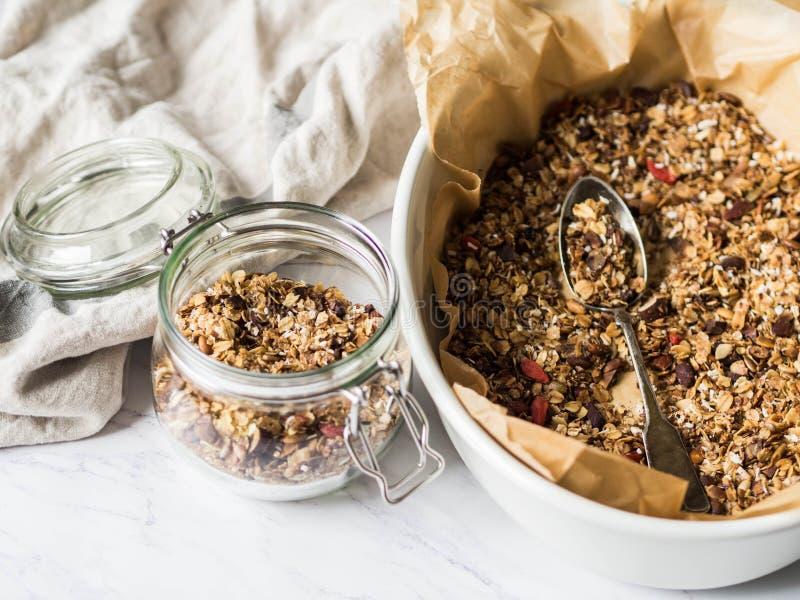 Гайки, семена, granola ягод goji в открытом стеклянном опарнике Здоровый завтрак - домодельный granola в опарнике на мраморной бе стоковое изображение rf