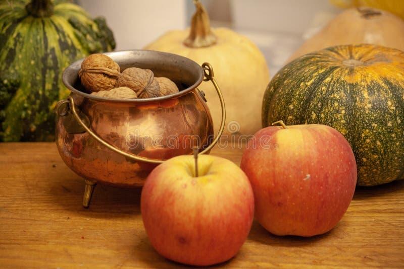 Гайки, яблоки и тыквы на деревянной доске стоковые изображения