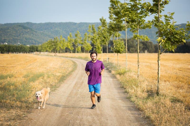 Гай бежать с собакой стоковое фото rf