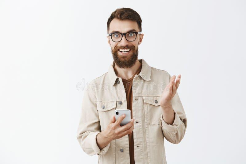 Гай возбудило новых характеристик smartphone описывая устройство к удерживающему приспособлению друзей в руках и показывать с лад стоковое фото rf