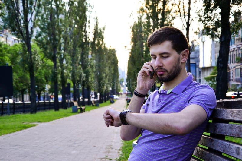 Гай вызывая на телефоне смотря вахту outdoors стоковые изображения
