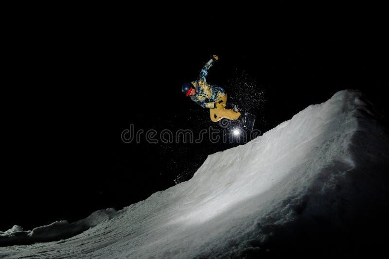 Гай в желтом костюме лыжи скача на сноуборд стоковые изображения rf