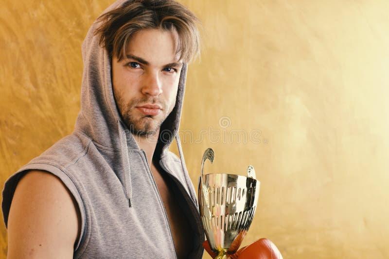 Гай в сером безрукавном hoodie держит золотой приз стоковая фотография
