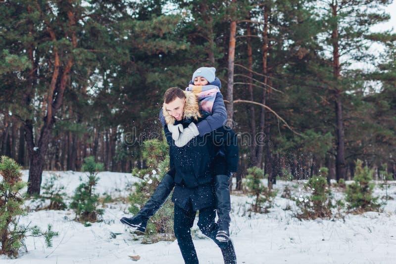 Гай давая его девушке автожелезнодорожные перевозки в парах Youn леса зимы любя имея потеху outdoors стоковая фотография rf