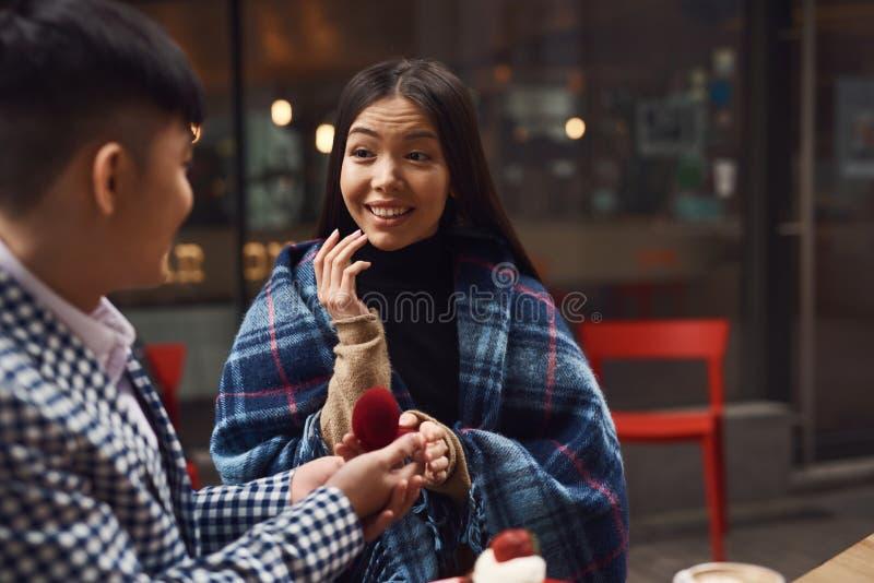 Гай делает предложение свадьбы к девушке сидя на таблице в кафе стоковые изображения rf