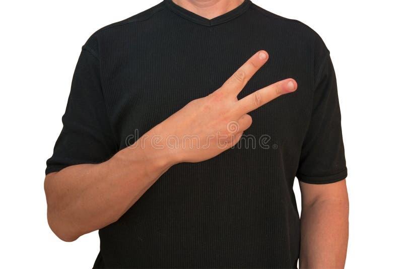 Гай держит руку на груди около сердца с v знаком пальцев Жест человека в черной футболке изолированной без стороны o стоковые изображения rf