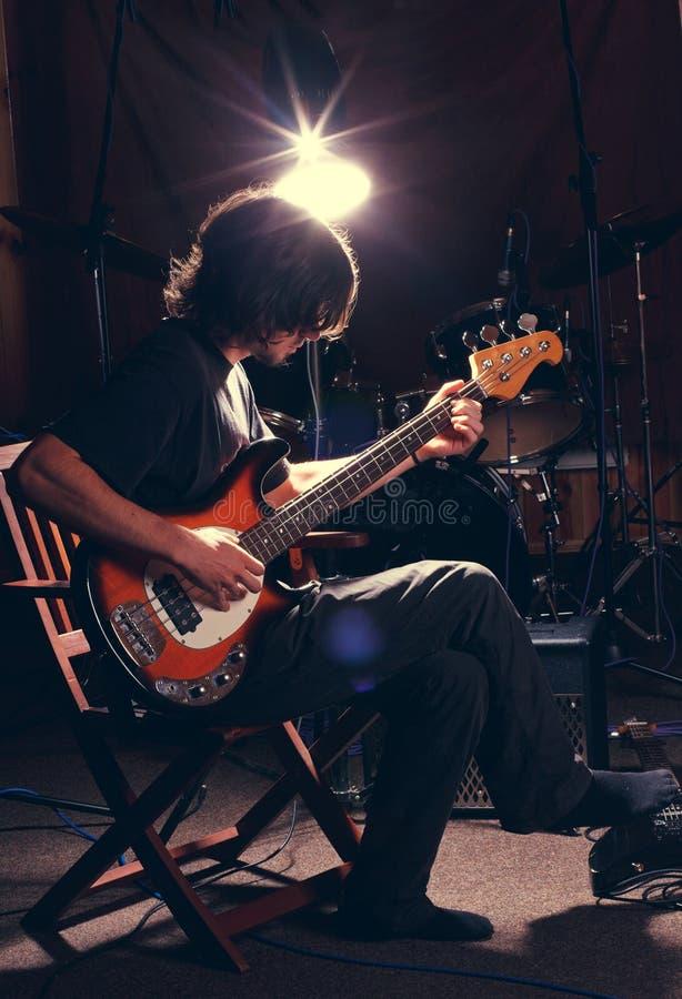 Гай играя басовую гитару стоковые фотографии rf