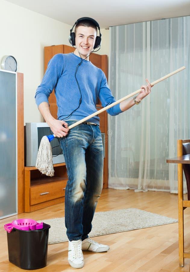Гай играя и очищая в комнате стоковое изображение rf