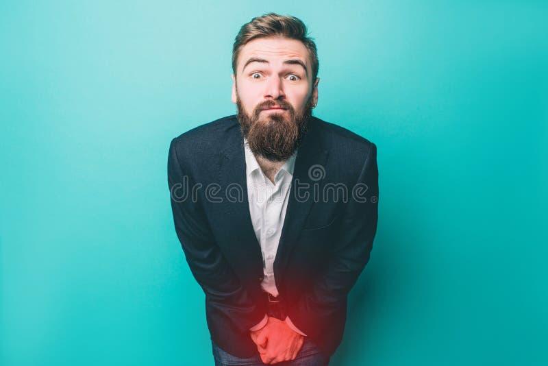 Гай имеет проблему с peeing Очень тягостно для его Изолировано на голубой предпосылке стоковые изображения