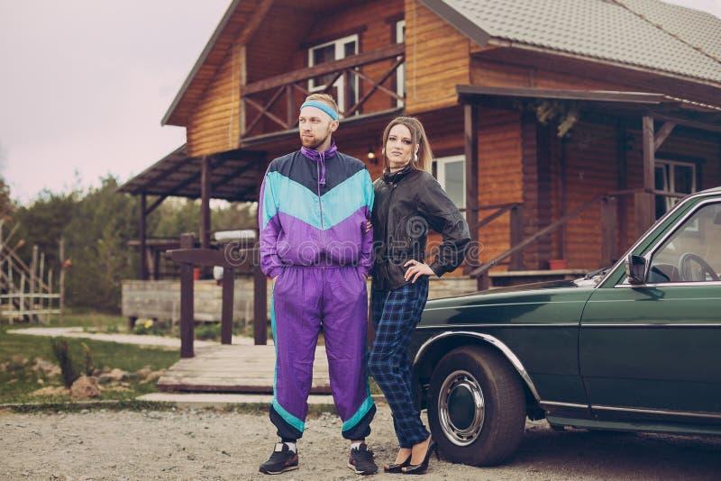 Гай и девушка в одеждах девяностых годов, рядом с старым автомобилем стоковые фотографии rf
