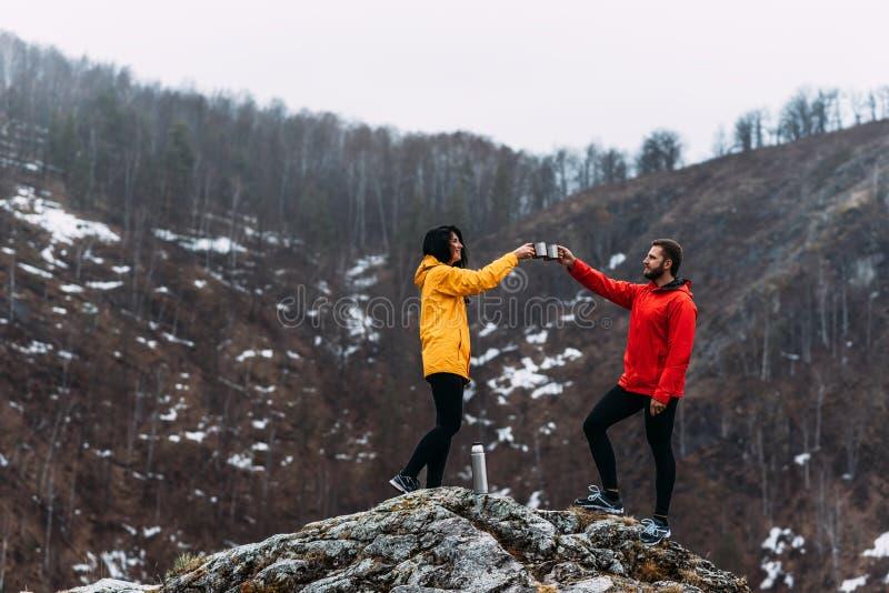 Гай и девушка путешествуя и выпивая горячий чай в горах стоковое фото rf