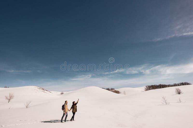 Гай и девушка путешествуя в горах в зиме стоковые фотографии rf