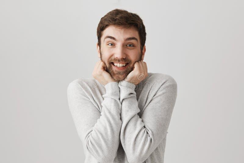 Гай не может контролировать его эмоции, хотеть обнять симпатичного щенка Портрет excited европейской мужской модели мельком взгля стоковое фото rf