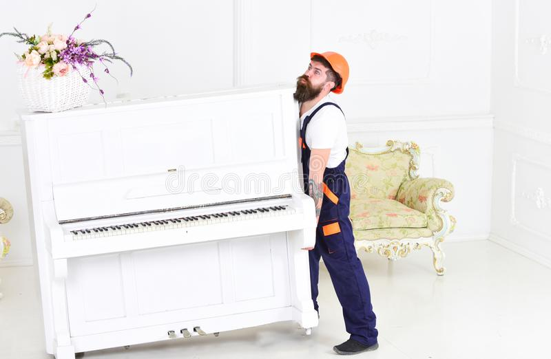 Гай от рояля транспортной компании moving старого самостоятельно Утомленный парень поднимая тяжелое вещество стоковое изображение