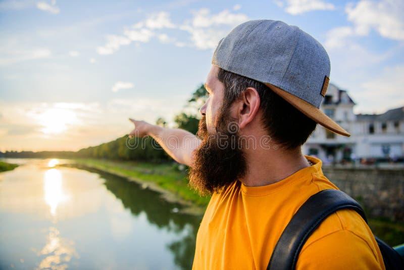 Гай перед голубым небом на времени вечера восхищает ландшафт Человек в крышке наслаждается заходом солнца пока стойка на мосте Мо стоковое фото rf