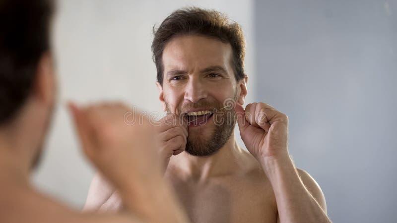 Гай позаботить о гигиена полости рта, чистя его зубы щеткой с зубоврачебной зубочисткой каждый день стоковая фотография rf