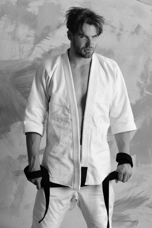 Гай представляет в белом кимоно держа черный пояс стоковое фото